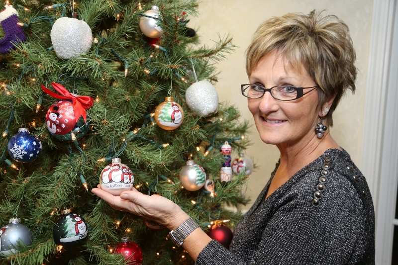 Donna Brandt holds one of the ornaments she personalized for  Oakwood Common residents Jane and Phil Button and their two dogs.